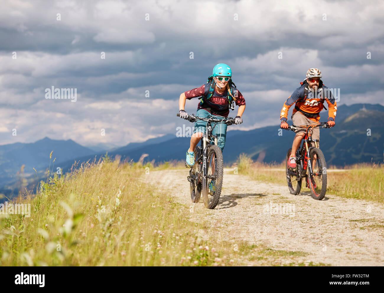 Two mountain bikers with helmets riding on gravel roads, Mutterer Alm near Innsbruck, Patscherkofel, Tyrol, Austria - Stock Image