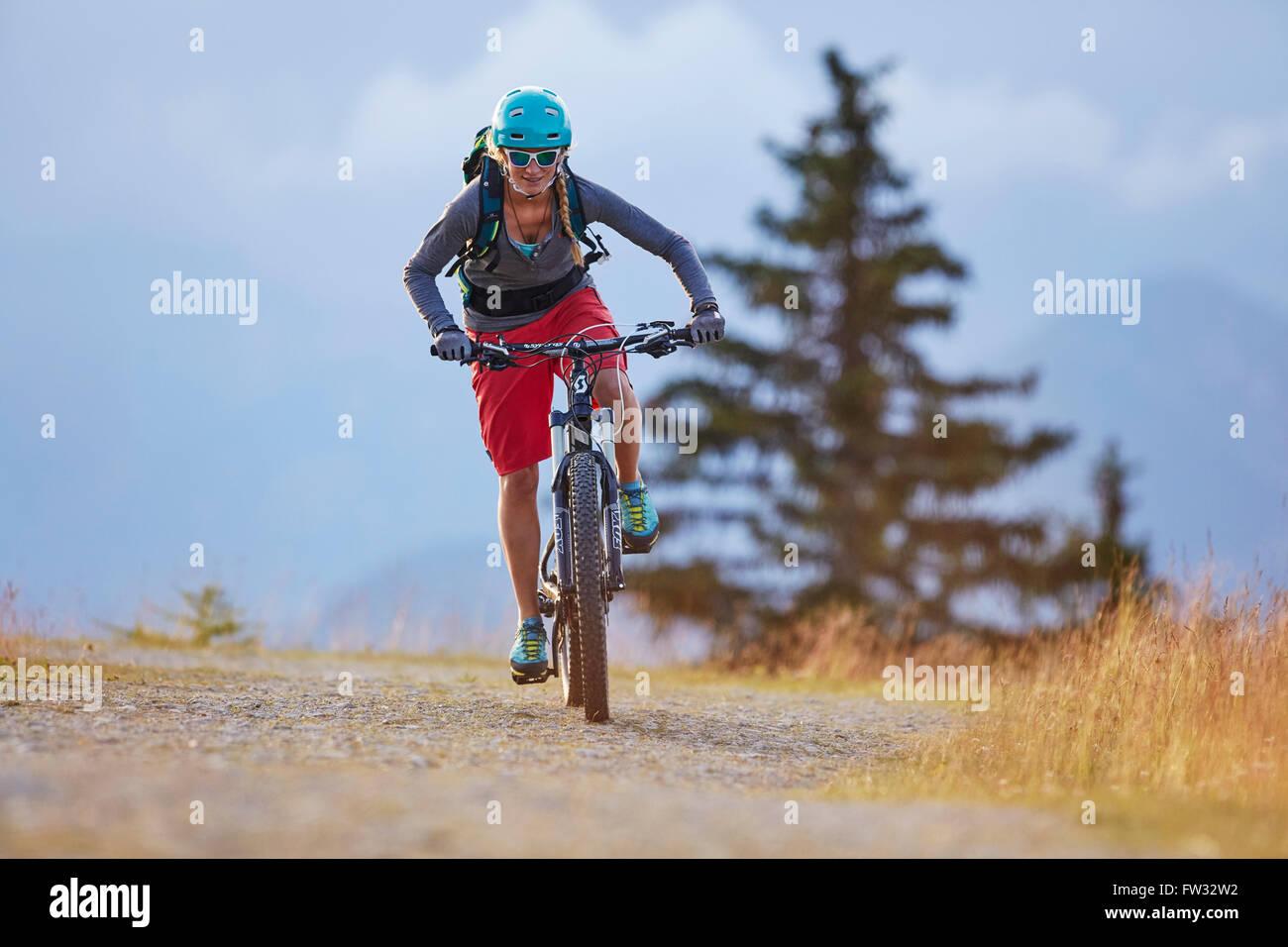 Mountain biker with a helmet riding on a gravel road, Mutterer Alm near Innsbruck, Tyrol, Austria Stock Photo