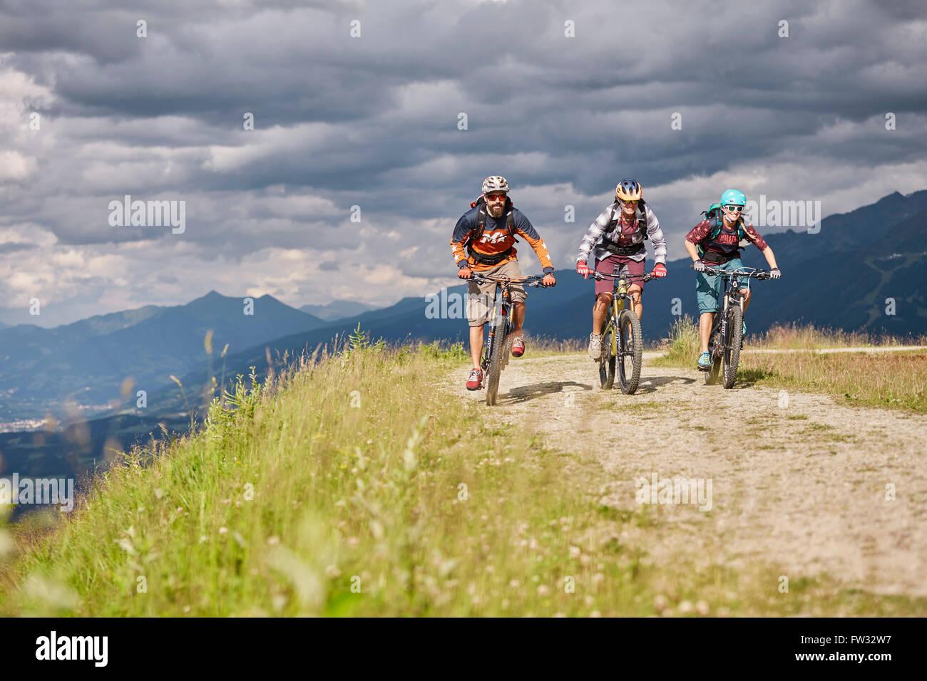Three mountain bikers with helmets riding on a gravel road, Mutterer Alm near Innsbruck, Tyrol, Austria - Stock Image
