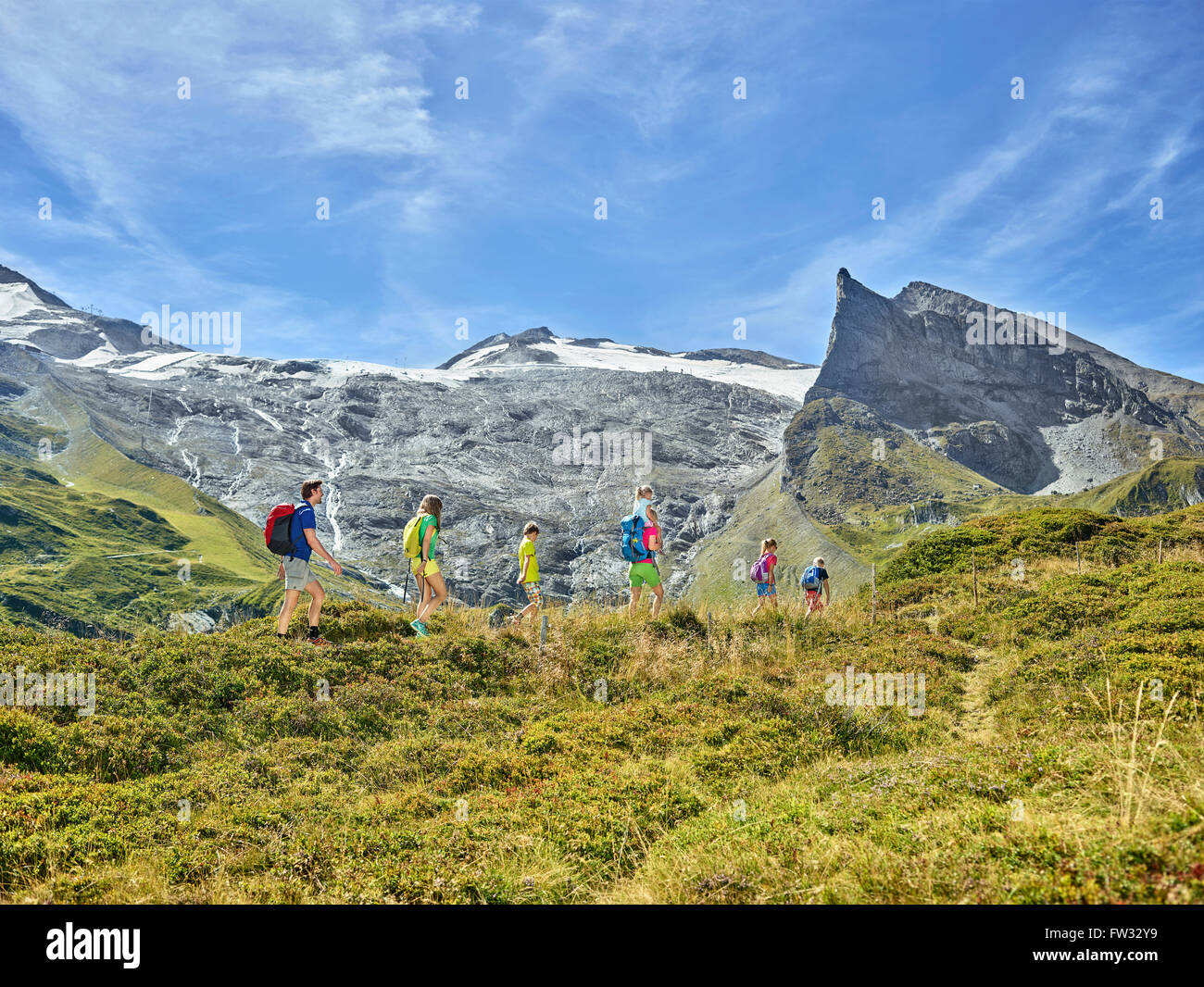 Family with five kids hiking in front of a mountain scenery, Hintertux, Zillertal, Tyrol, Austria - Stock Image