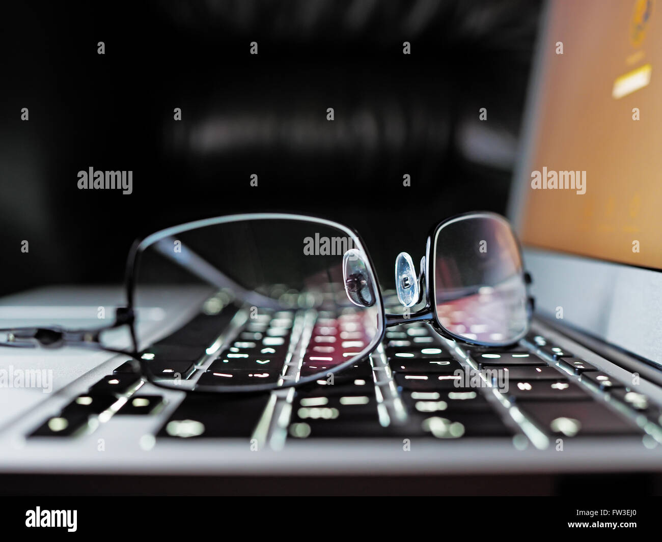 Reading eyeglasses on an elegance laptop keyboard, shallow depth of field - Stock Image