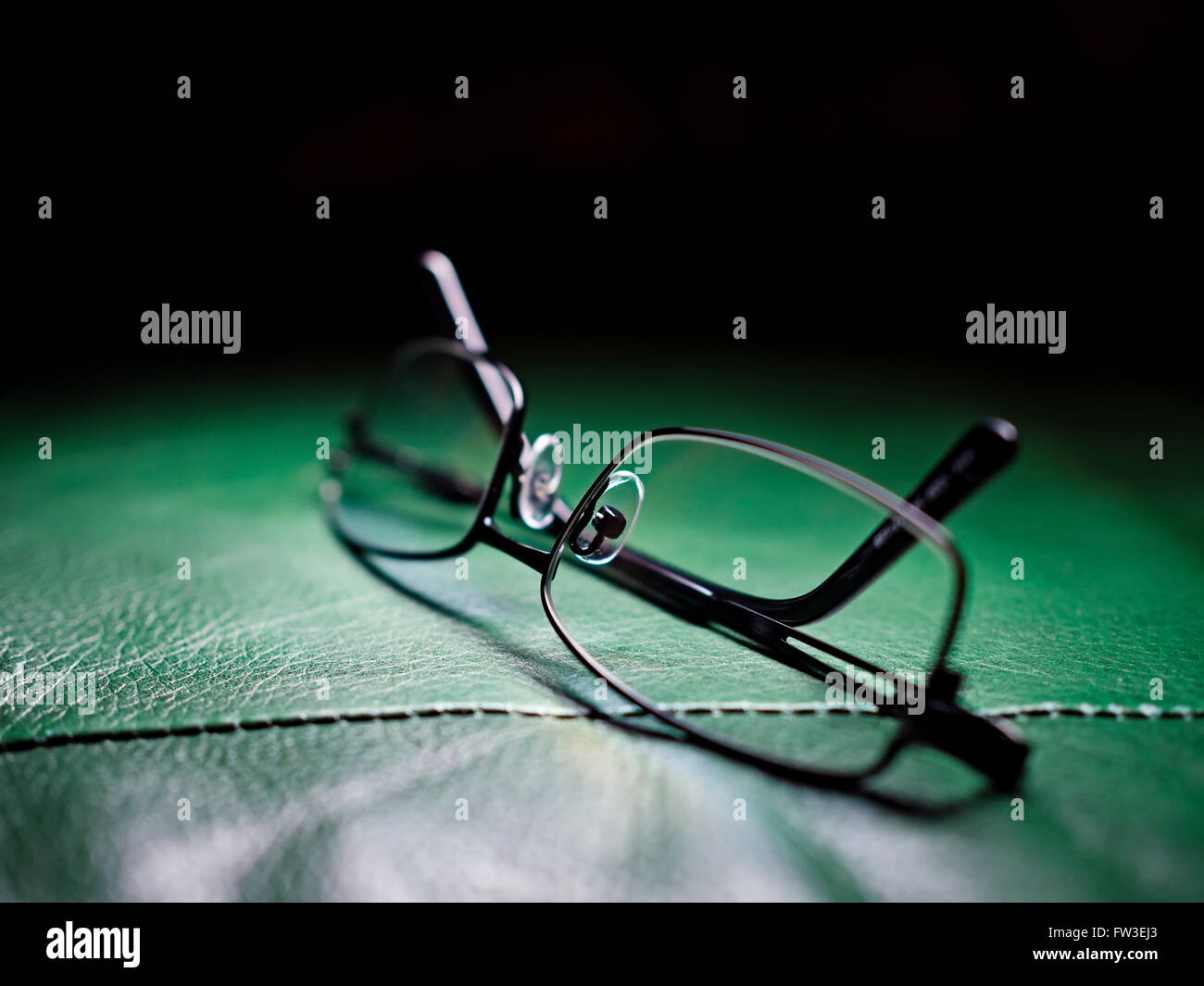 Reading glasses on the leather armchair, shallow depth of field - Stock Image