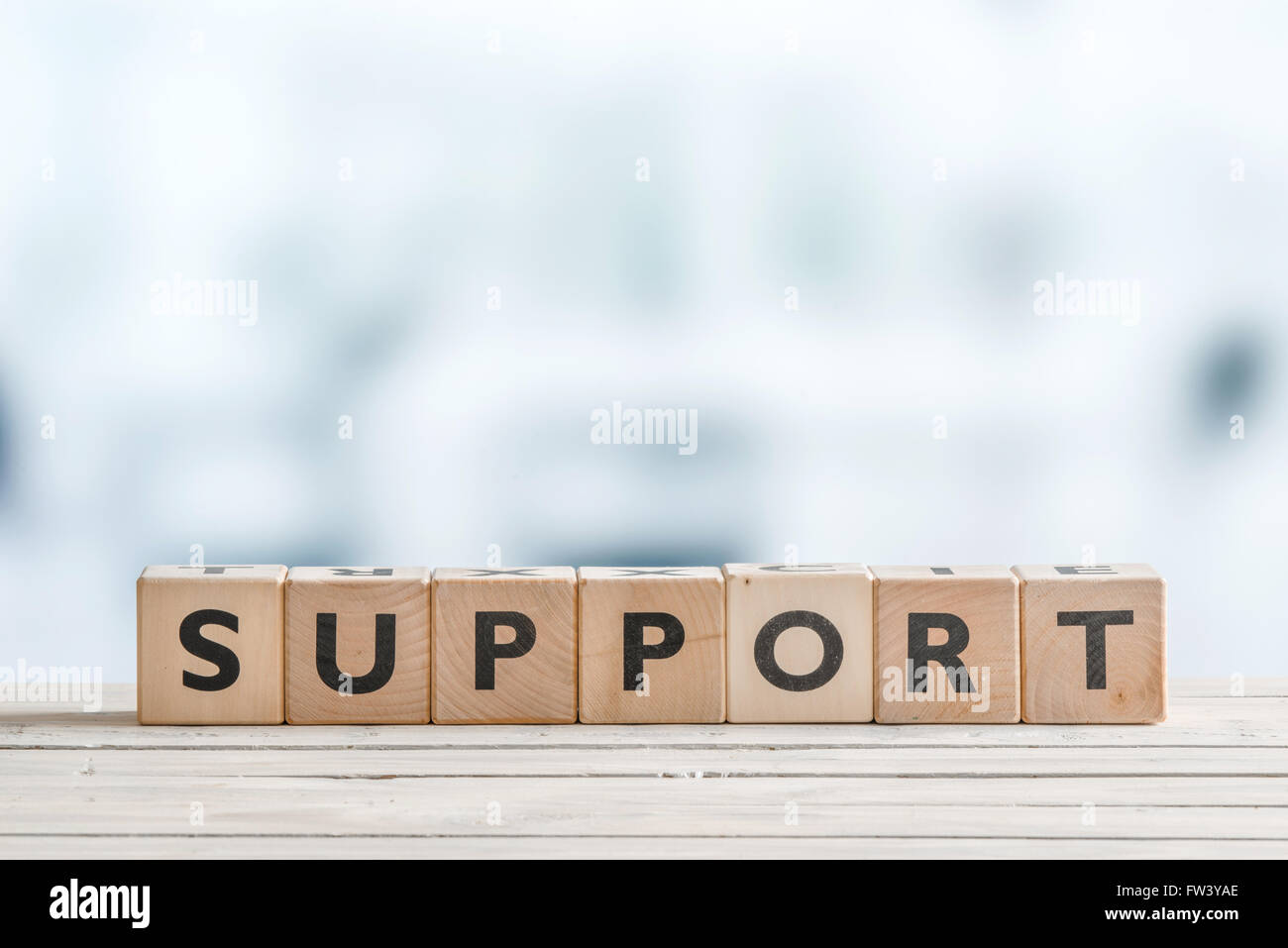 Support sign with blocks on a wooden office desk - Stock Image