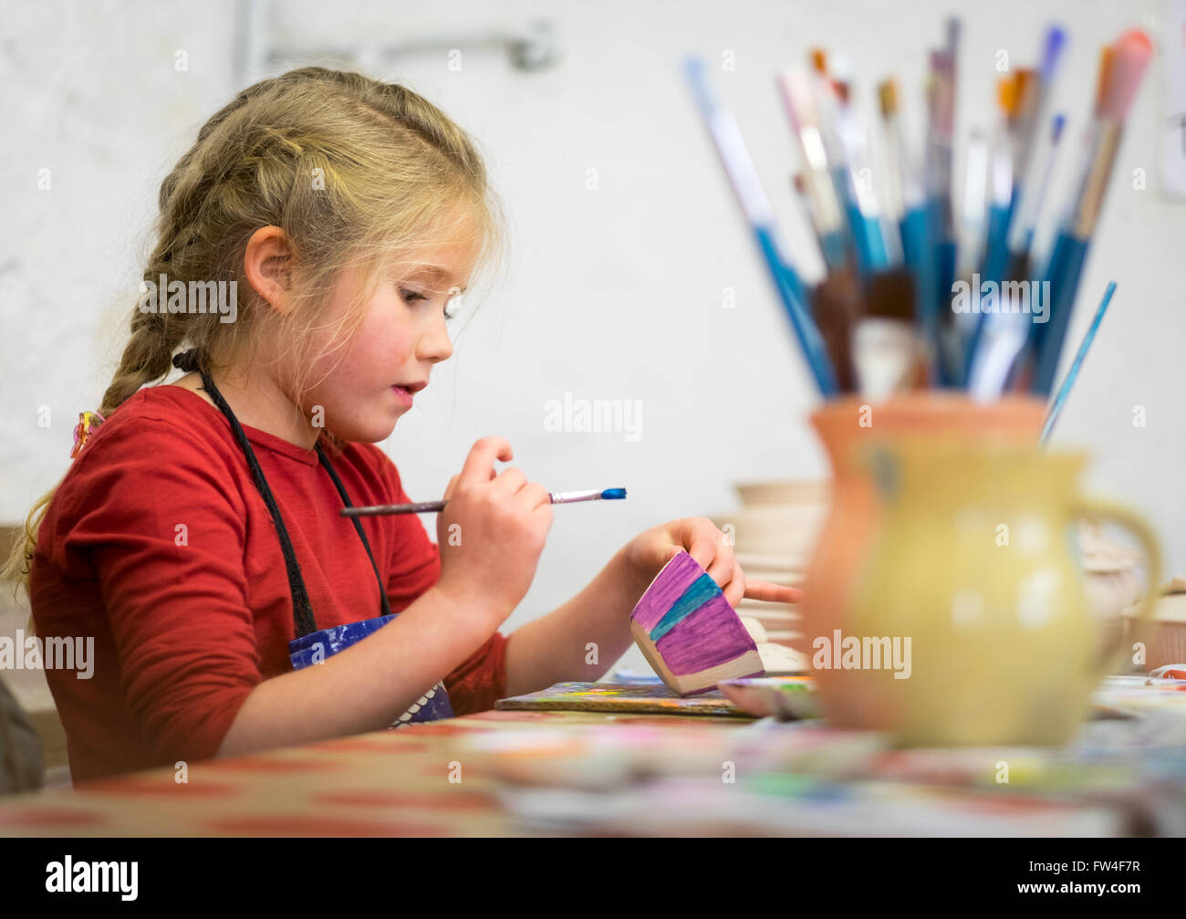 A young girl hand painting a pot in an art studio - Stock Image