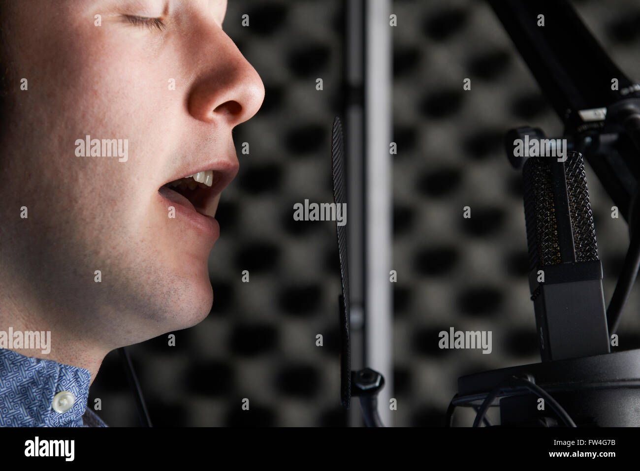 Male Vocalist With Microphone In Recording Studio - Stock Image