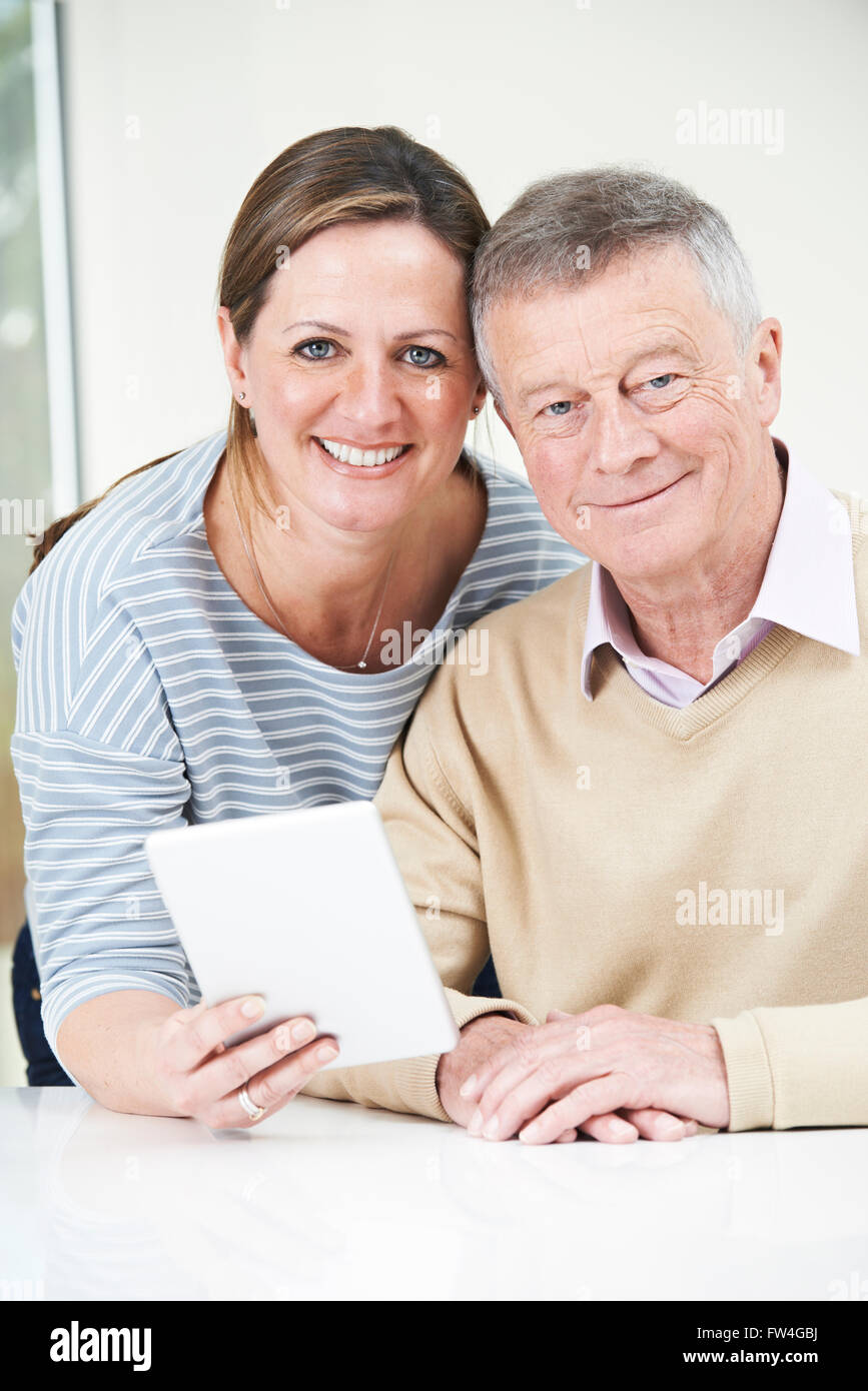 Senior Man And Adult Daughter Looking At Digital Tablet Together - Stock Image