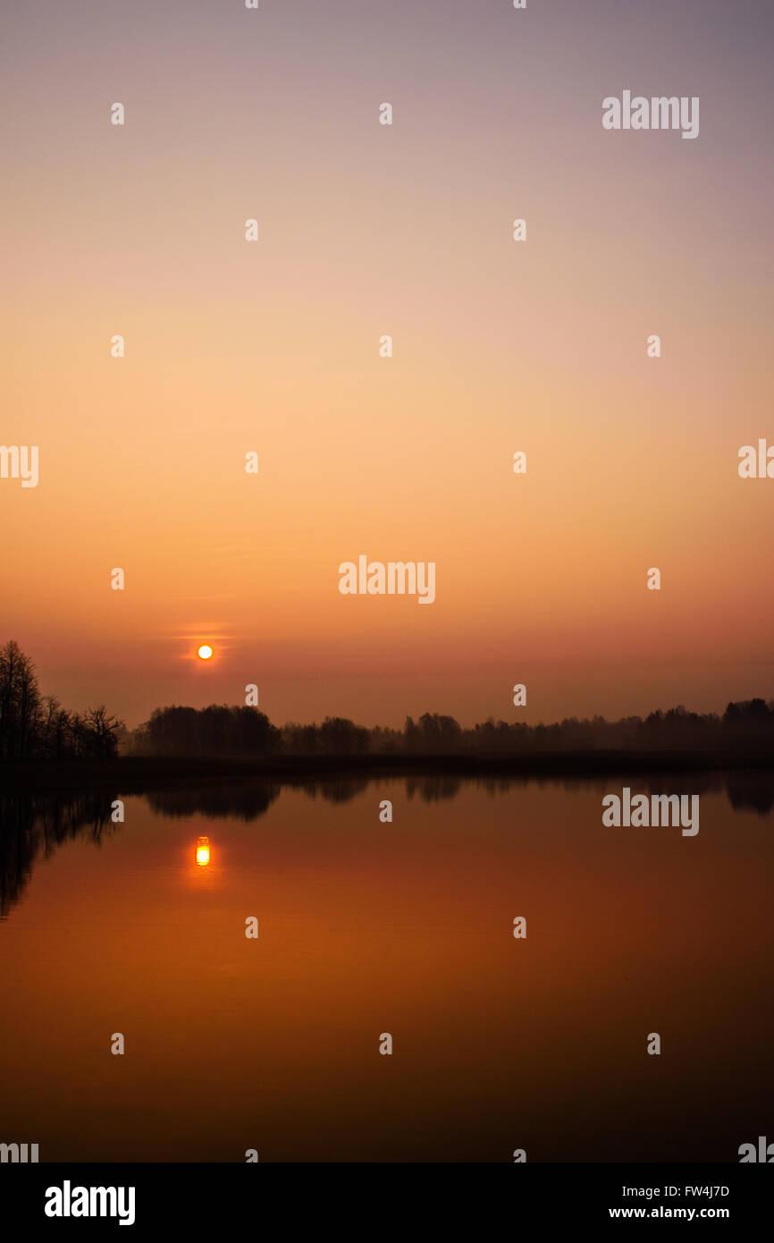 sunrise over still water - Stock Image
