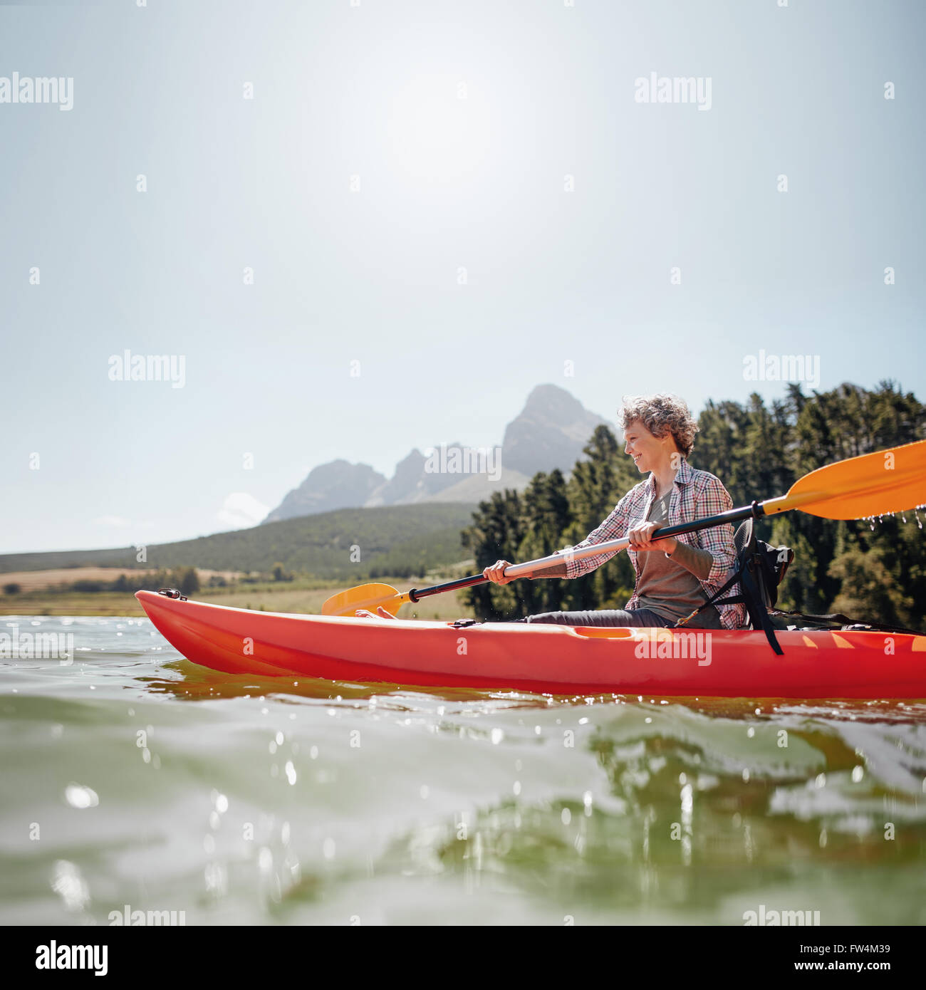 Portrait of a mature woman with kayak in a lake. Senior woman paddling kayak on a summer day. - Stock Image