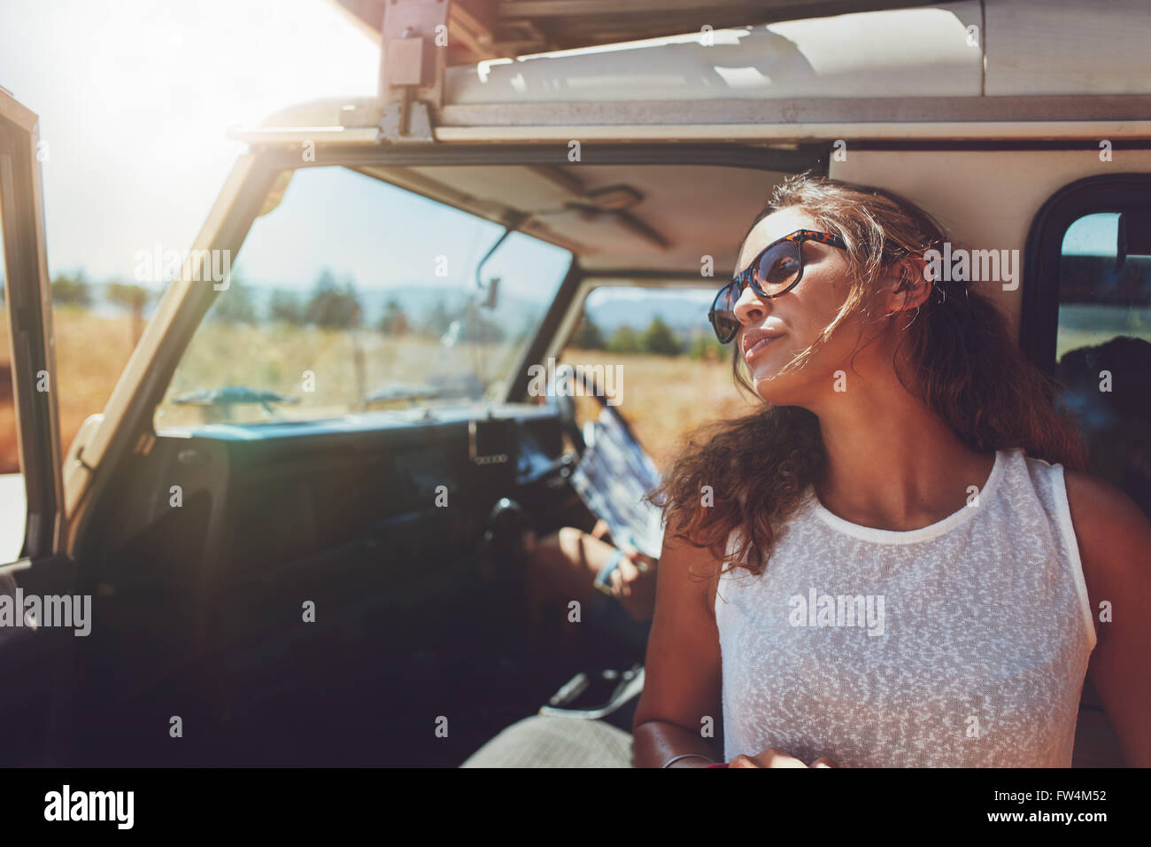 Young woman standing outside the car. Woman taking a break from the road trip. - Stock Image