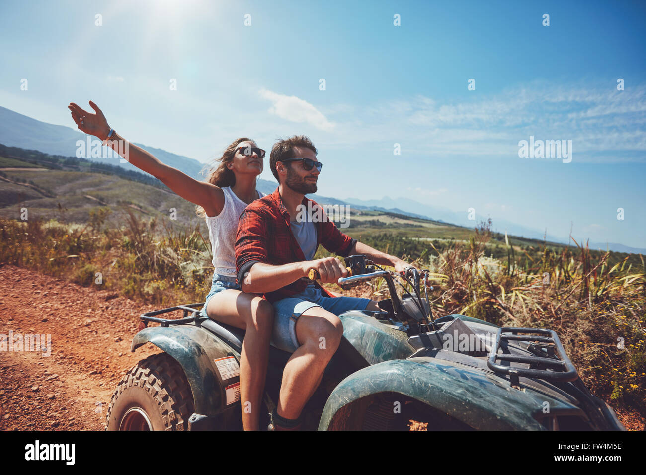 Happy young couple in nature on a quad bike. Young man and woman enjoying a quad bike ride in countryside. Man driving - Stock Image