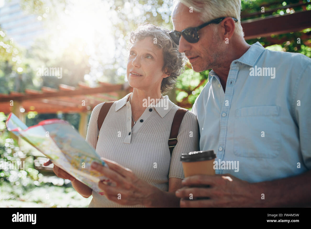 Close up portrait of senior couple using a map for directions. Retired couple exploring new places to visit during - Stock Image