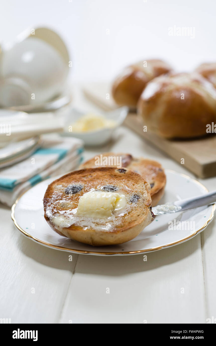 Toasted homemade hot cross buns with melting butter placed on a cream wooden table. - Stock Image