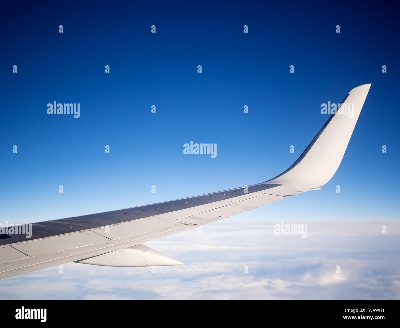 Airliner wing, clouds and blue sky copy space - Stock Image