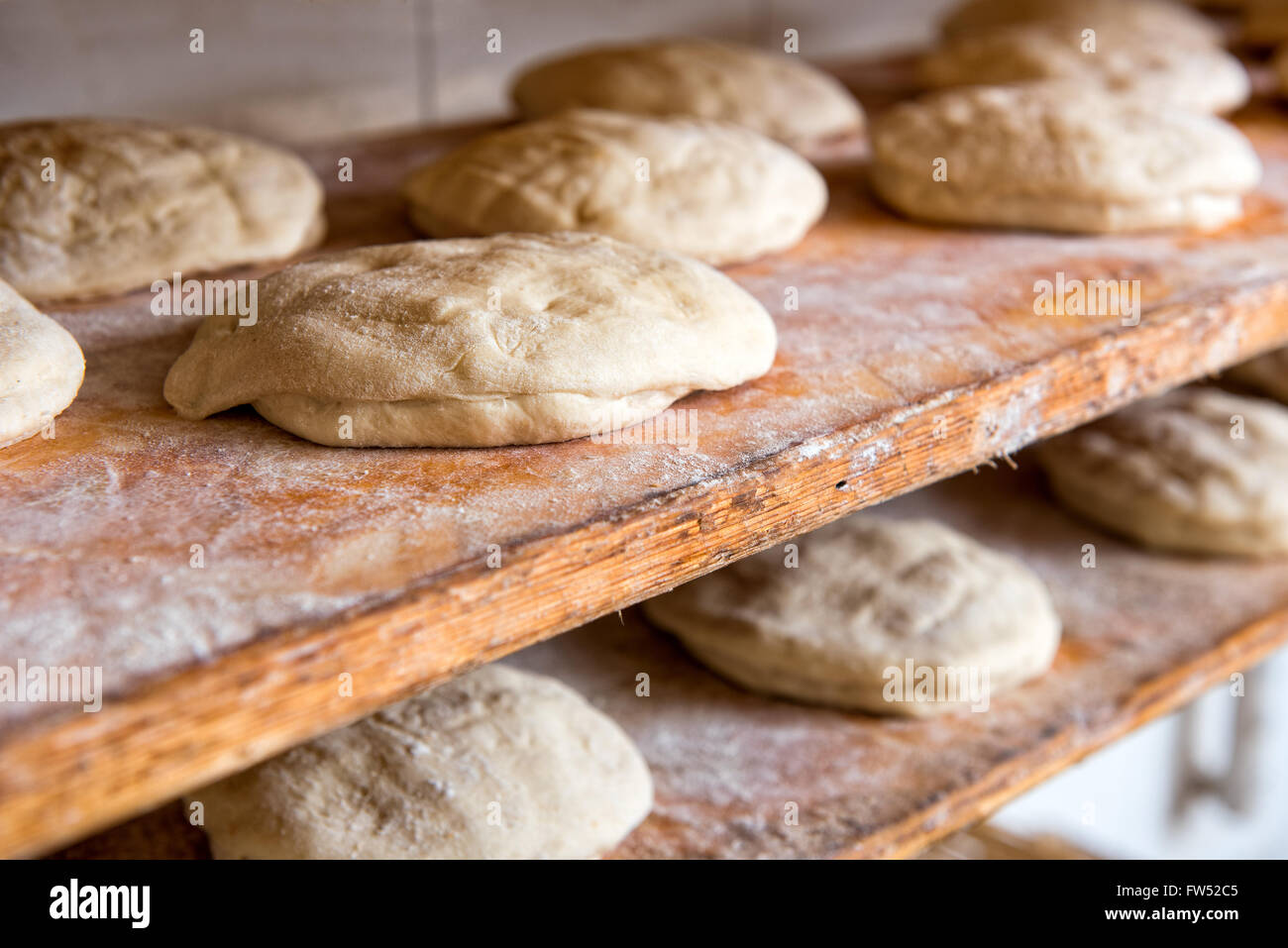 Prepared raw bread dough shaped into loaves on wooden shelves ready to go into the oven in a bakery, close up view - Stock Image