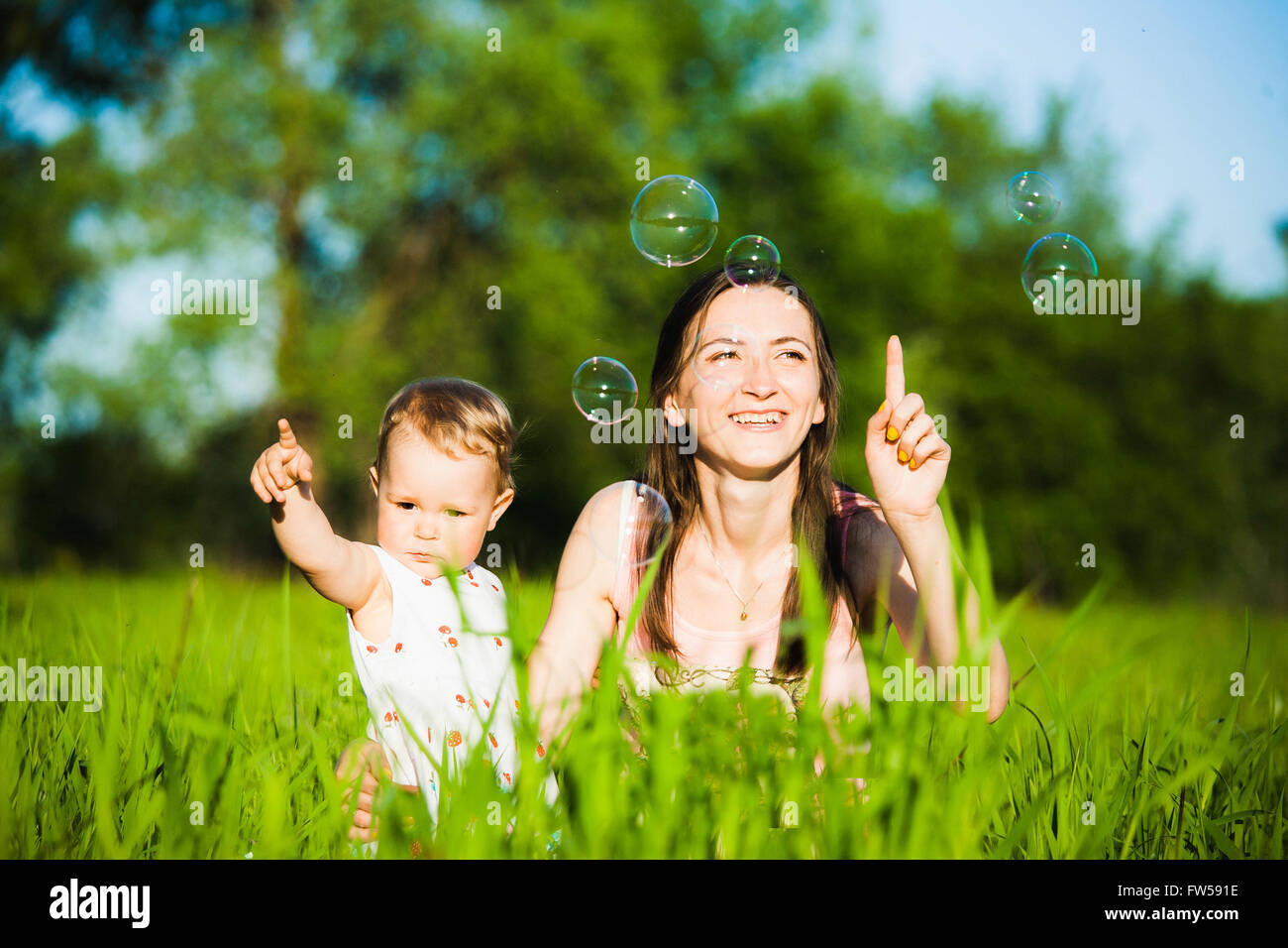Mom and baby girl laying on grass and cheerfully catching soap bubbles with fingers. Happy family concept. - Stock Image