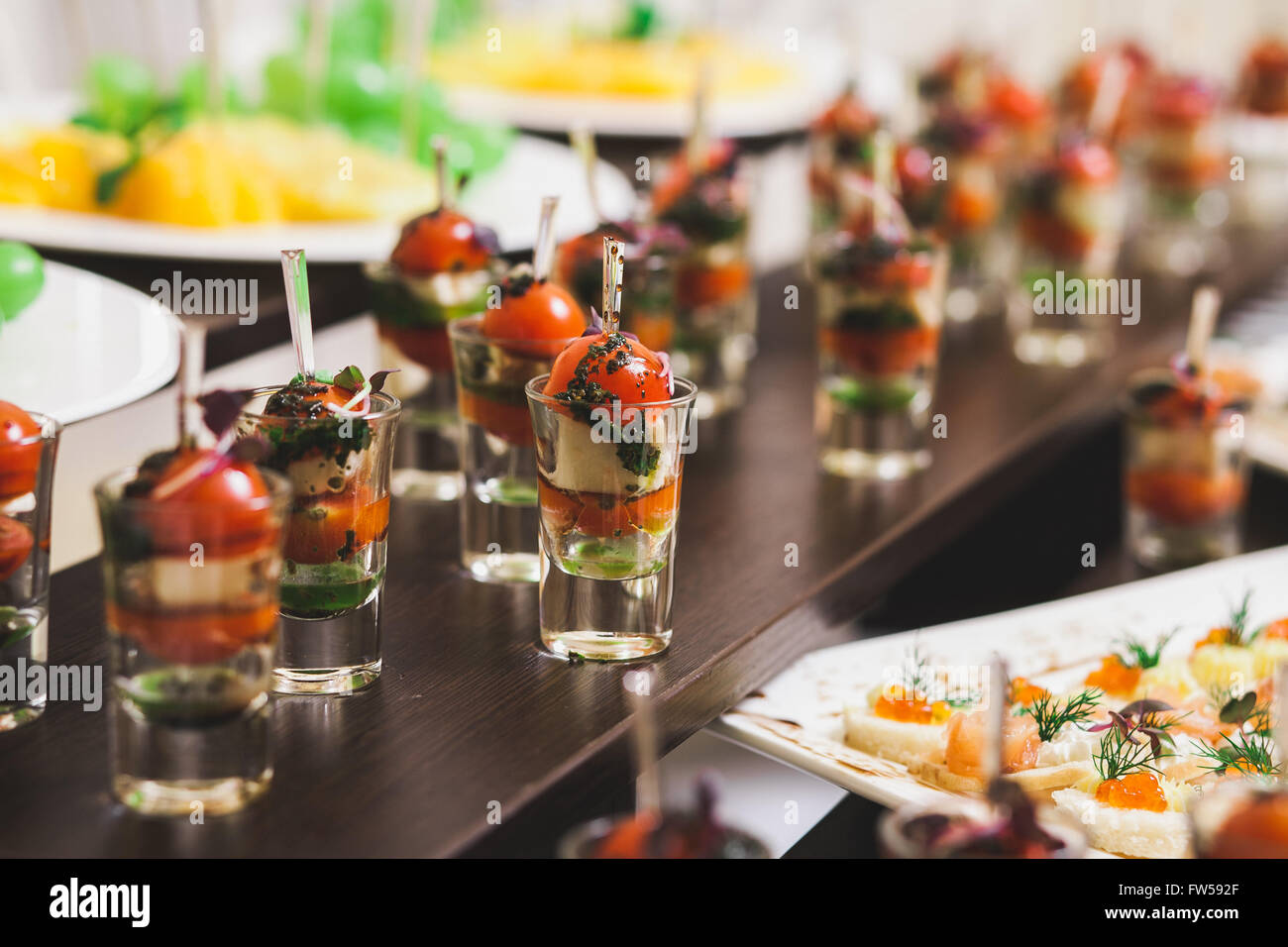 Catering for party. Close up of sandwiches, appetizers and fruit - Stock Image