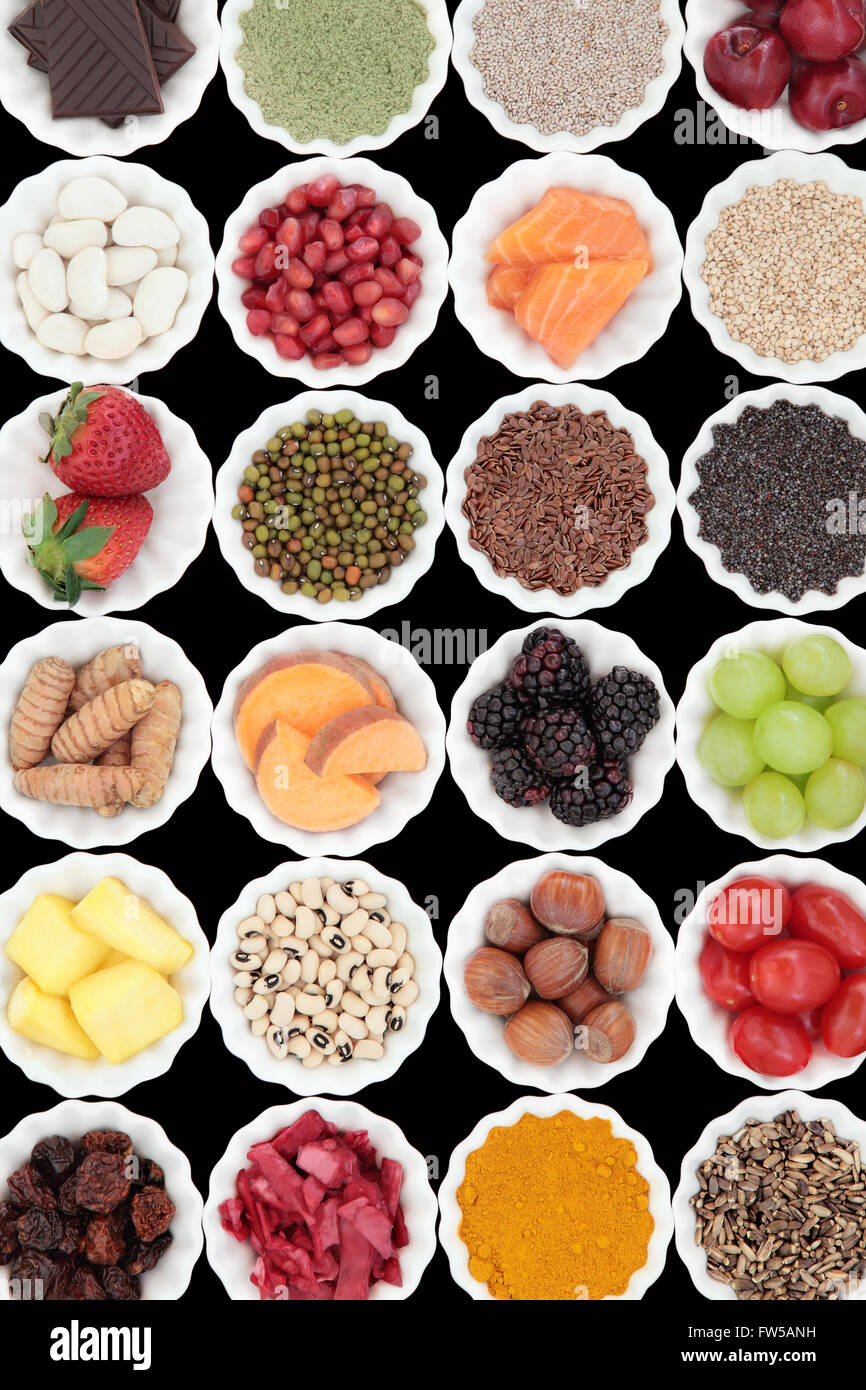 Super food collection in porcelain crinkle bowls over black background. High in vitamins and antioxidants. - Stock Image