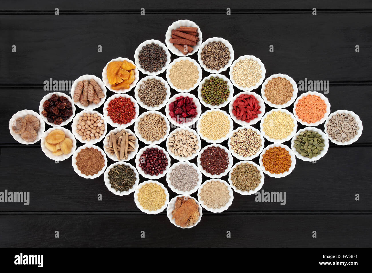 Large dried health food sampler in china bowls forming an abstract background. High in antioxidants, minerals and - Stock Image