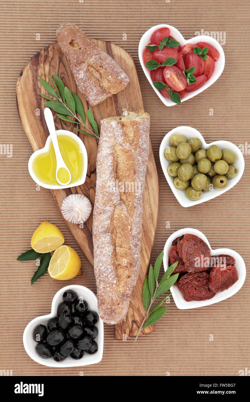 French baguette bread on an olive wood board with fresh and sun dried tomatoes, green and black olives and oil in - Stock Image