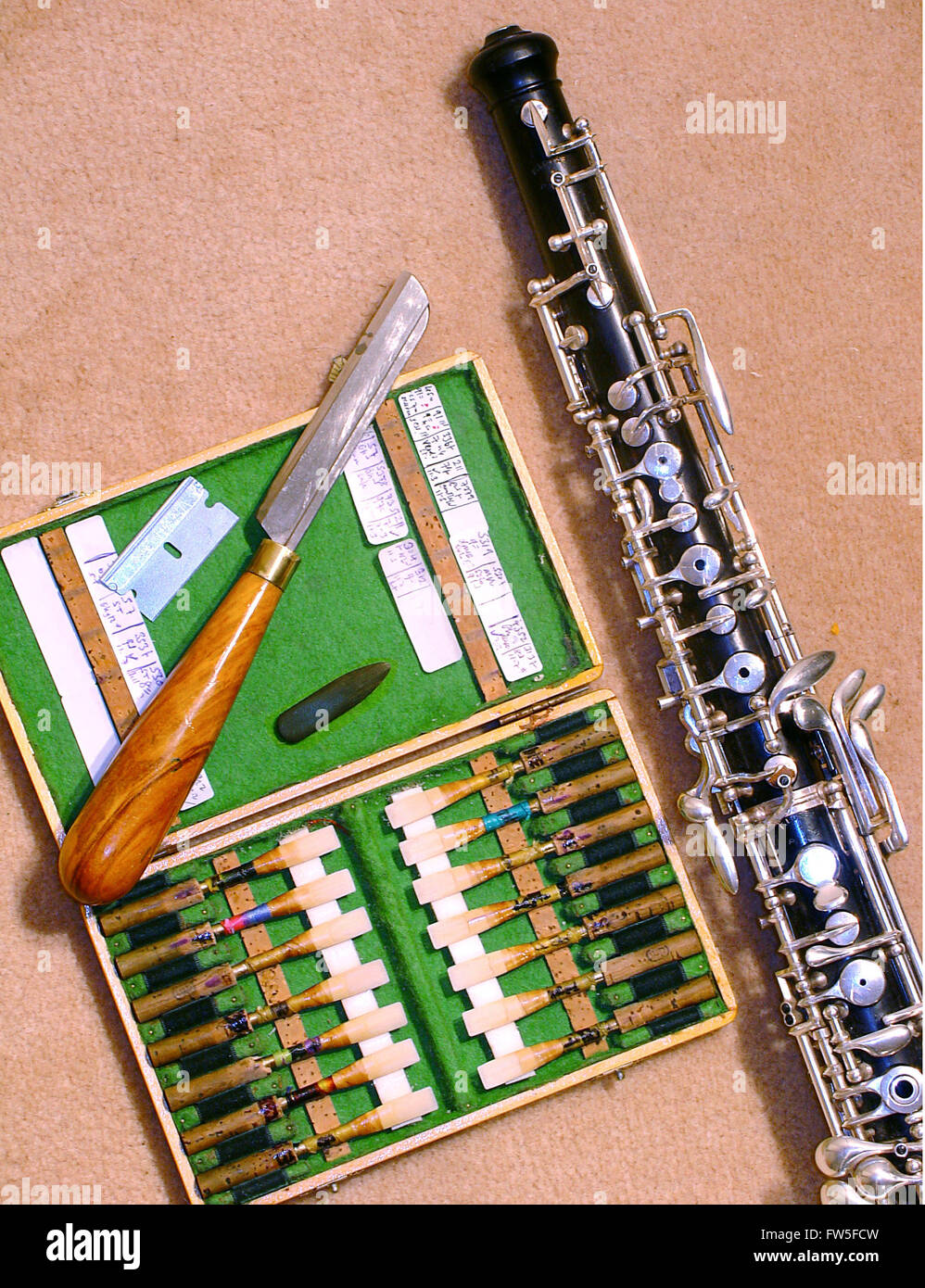 Oboe with box of reeds, scraping knife, 'tounge', and razor blade. Written notes refer to history of usage. Stock Photo