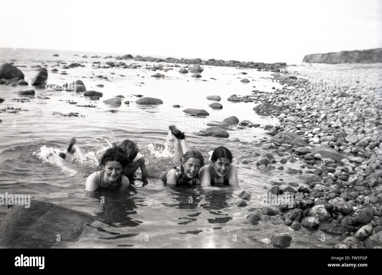 1930s historical, young girls lying in rock pools by beach. - Stock Image
