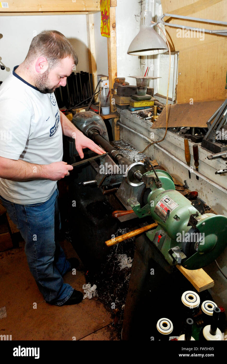 Bagpipe maker turning wooden 'billet' for chanter, on lather. The Royal Mile, Canongate, Edinburgh - Stock Image