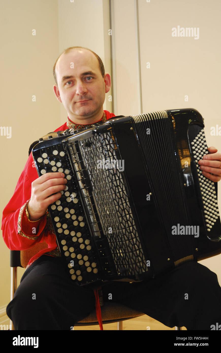 Accordion played by Nikolai Ryskov, in red Russian costume - Stock Image