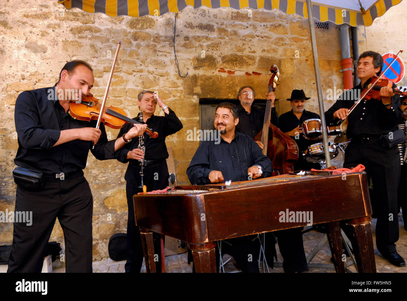 violinist with Romanian gypsy  band, busking in France, with cimbalom (a 'concert hammer dulcimer'), Rumanian - Stock Image