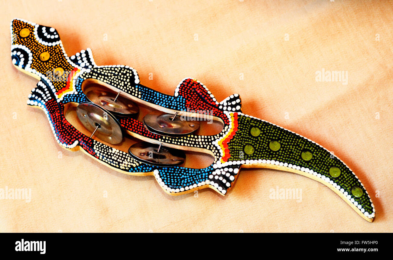 folk percussion rattle from India, in form of lizard, painted in Australian aboriginal design, with small cymbals - Stock Image