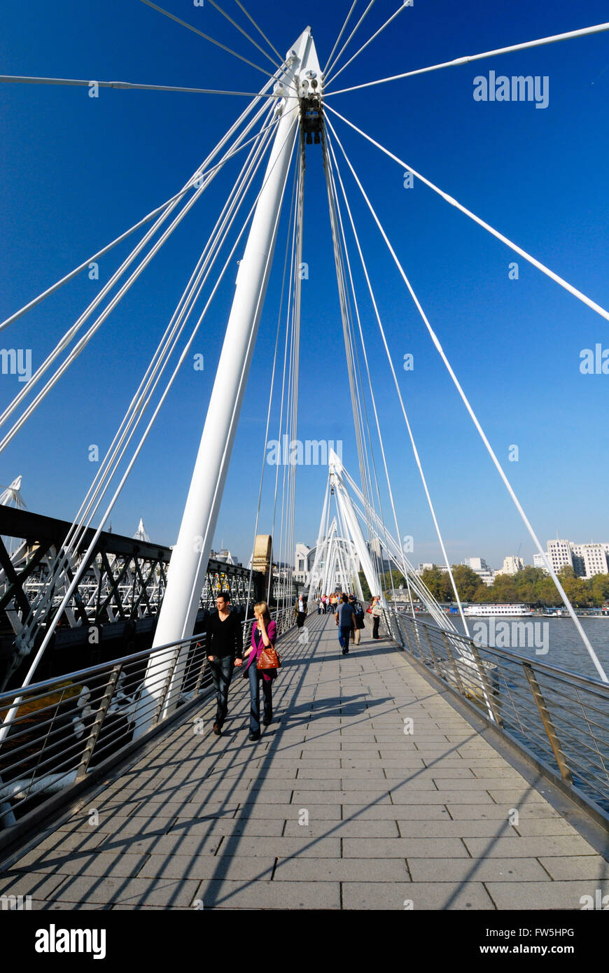 new Hungerford Bridge, foot bridge linking London's South Bank with the West End, with pedestrians crossing - Stock Image