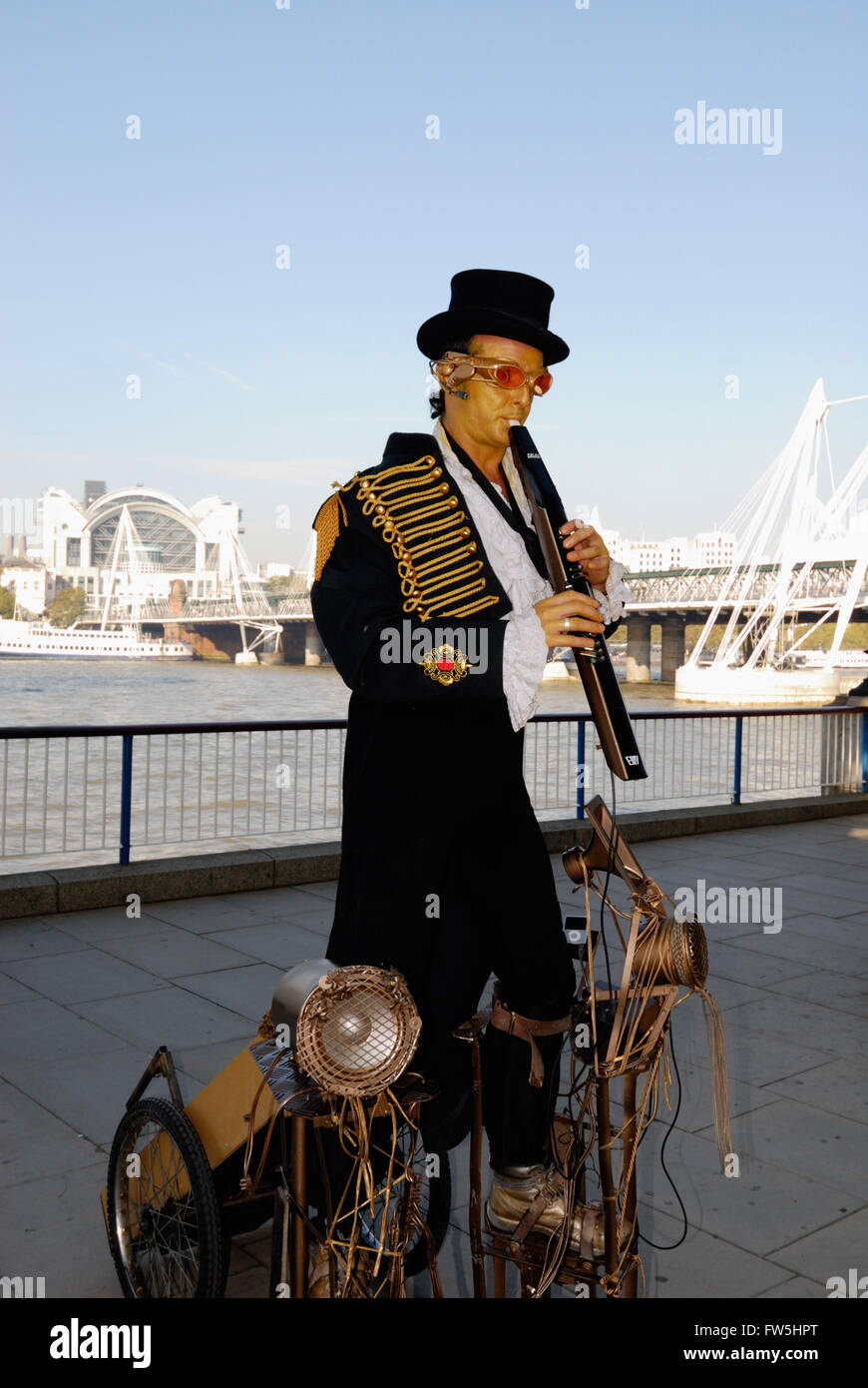 Whistler Dan, busker playing Akai MIDI wind instrument, on London's Southbank walkway, in front of Royal Festival - Stock Image