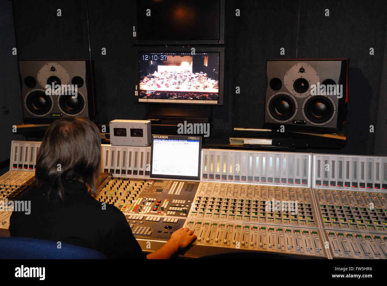 48 channel mixing desk of BBC outside broadcast recording van, with sound engineer balancing orchestral concert - Stock Image