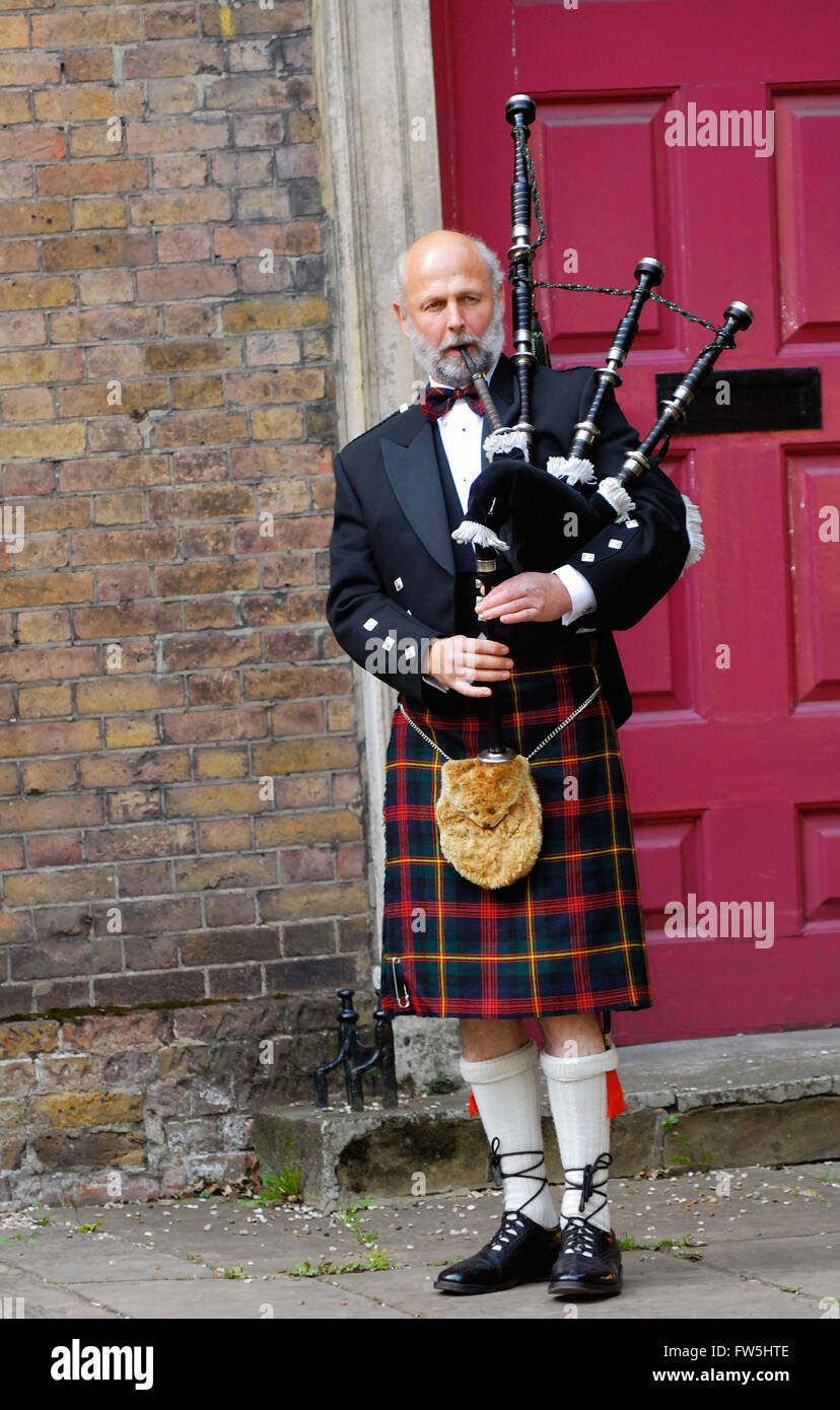 bagpiper in kilt, outside church door, playing for exit of bride and groom at wedding, Hampstead London NW3. Landscape Stock Photo