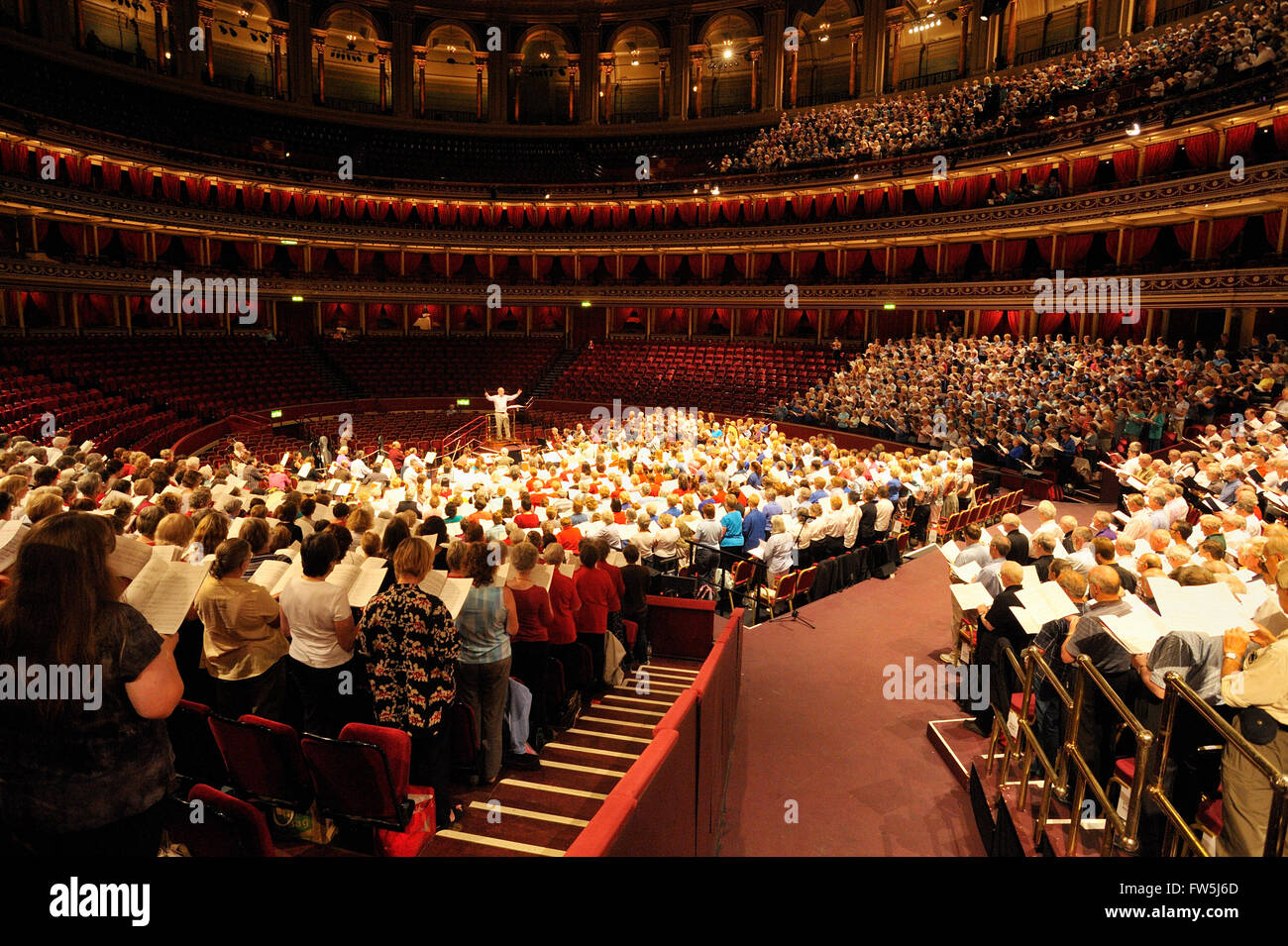 The Really Big Chorus, for Concerts from Scratch, rehearsing with conductor John Rutter, composer and editor, his - Stock Image