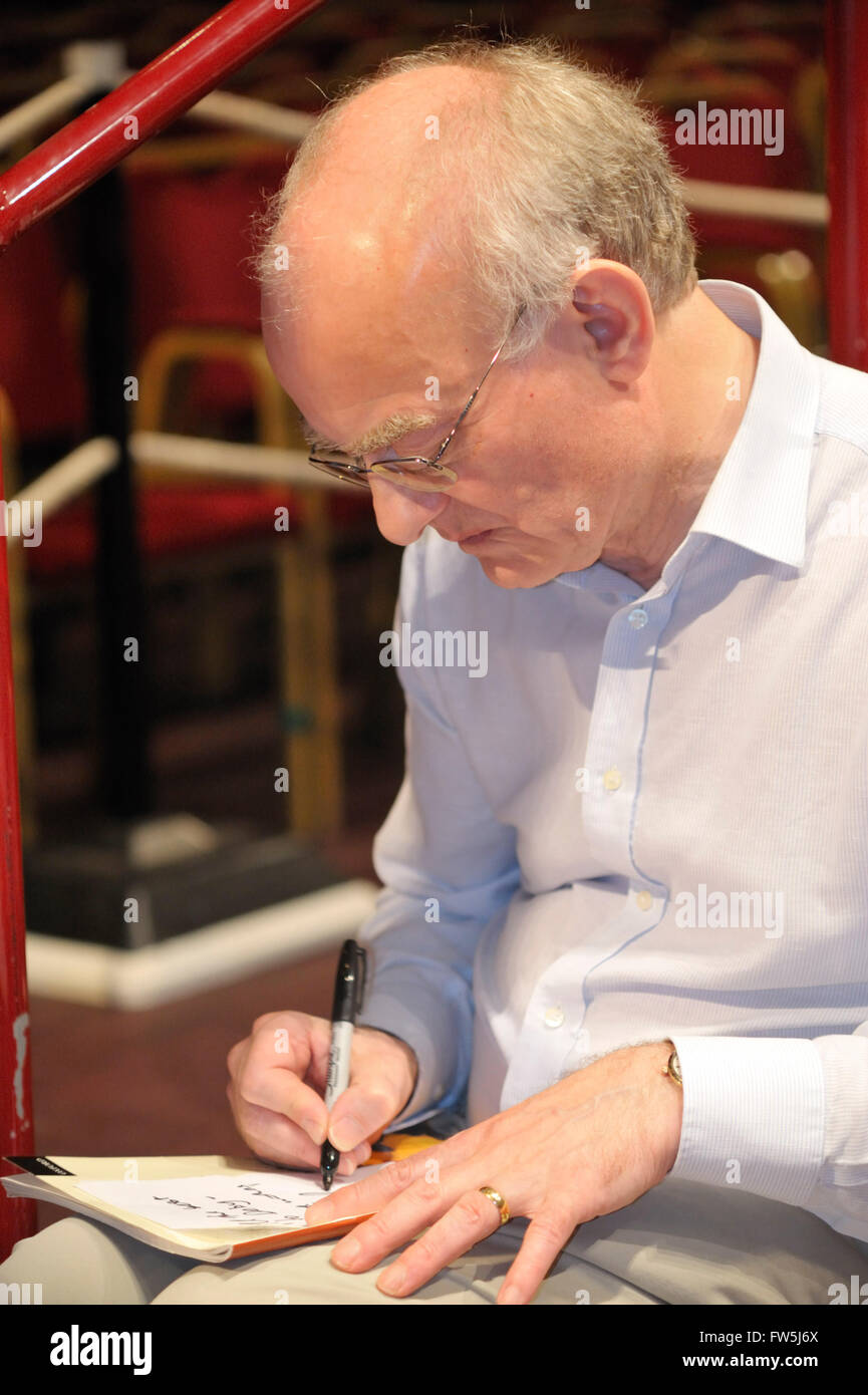 John Rutter, composer and editor, signing copies of the score before conducting his Requiem in the Royal Albert - Stock Image