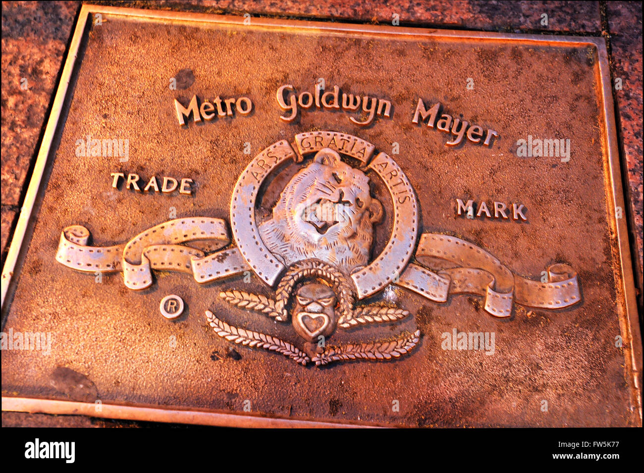 Metro Goldwyn Mayer bronze plaque in the pavement of Leicester Square: of Metro-Goldwyn-Mayer Inc., MGM, American - Stock Image