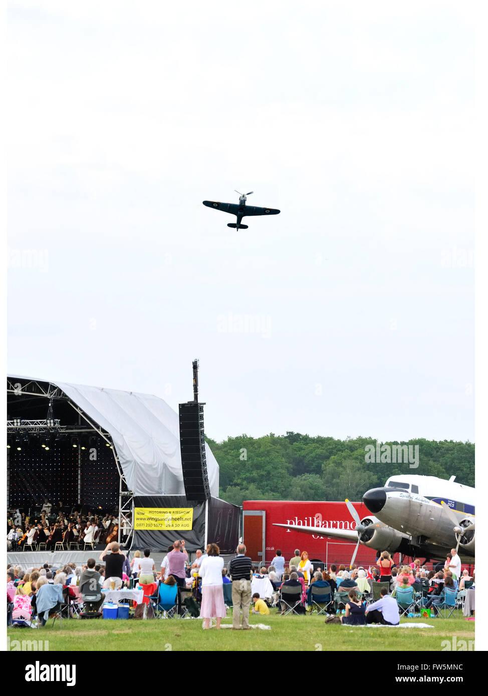A World War 2 Hurricane does aerobatics over open-air concert in Dunsfold Aerodrome, nr. Cranleigh, Surrey. Concert - Stock Image