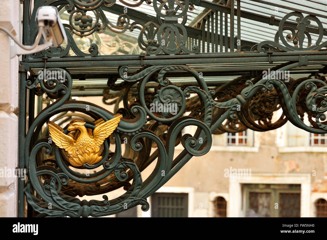 Phoenix, La Fenice. Golden phoenix on ornate cast iron work of the new opera house La Fenice in Venice, reopened - Stock Image