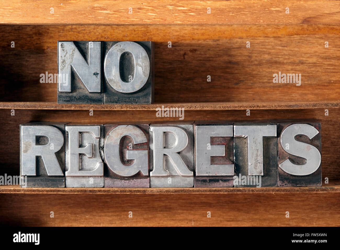 no regrets phrase made from metallic letterpress type on wooden tray - Stock Image