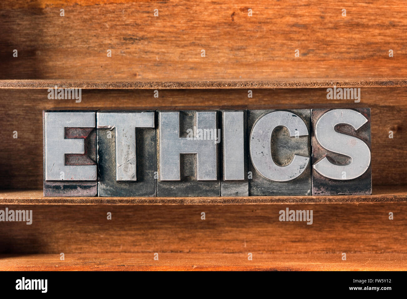 ethics word made from metallic letterpress type on wooden tray - Stock Image