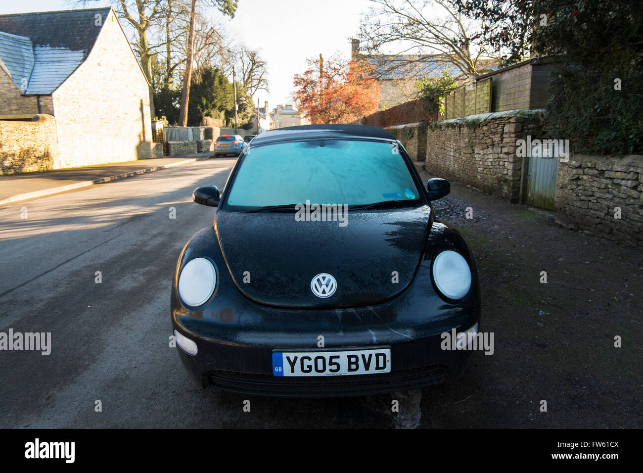 Black VW Beetle Cabriolet with frosty windscreen and headlights parked in Gloucestershire, UK - Stock Image