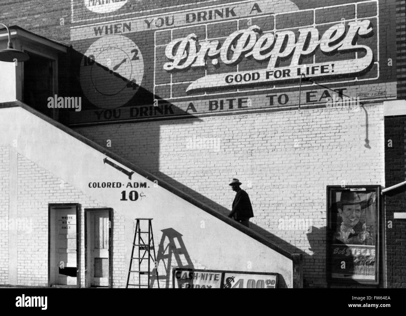 Racial Segregation. A black man going up a stairway to the 'colored' entrance of a movie theater with a - Stock Image