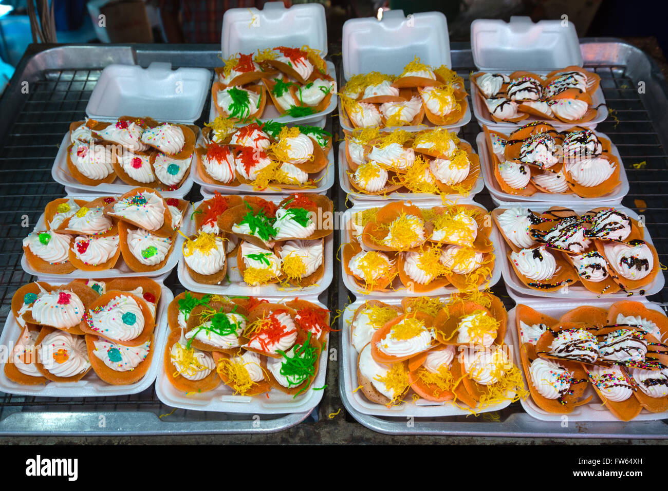 Market stall with various Thai sweets, food stall, food for sale at a night market, Thailand - Stock Image