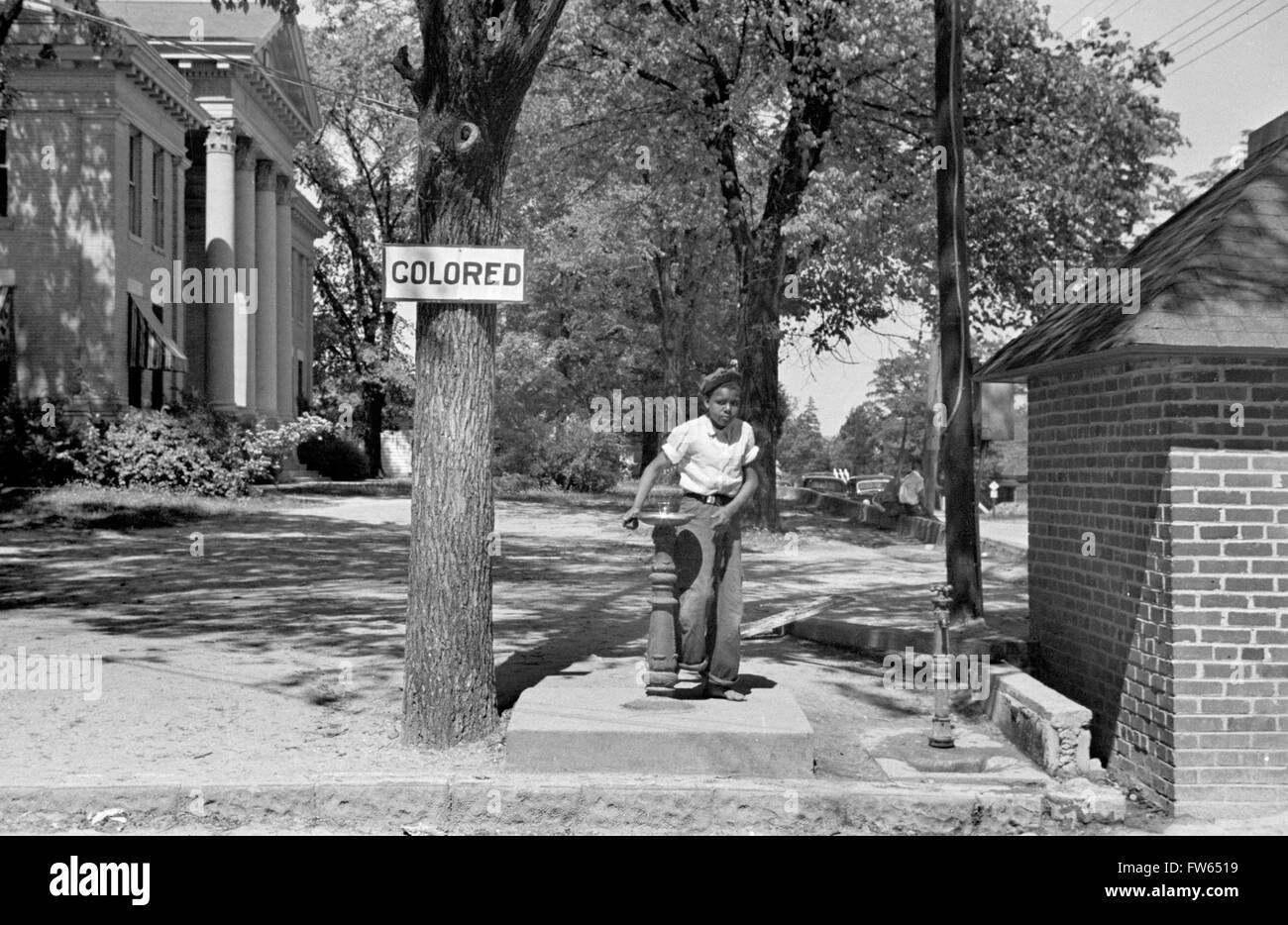 Segregation, USA. Young black boy drinking at a water fountain with a 'Colored' sign above it, Halifax, - Stock Image