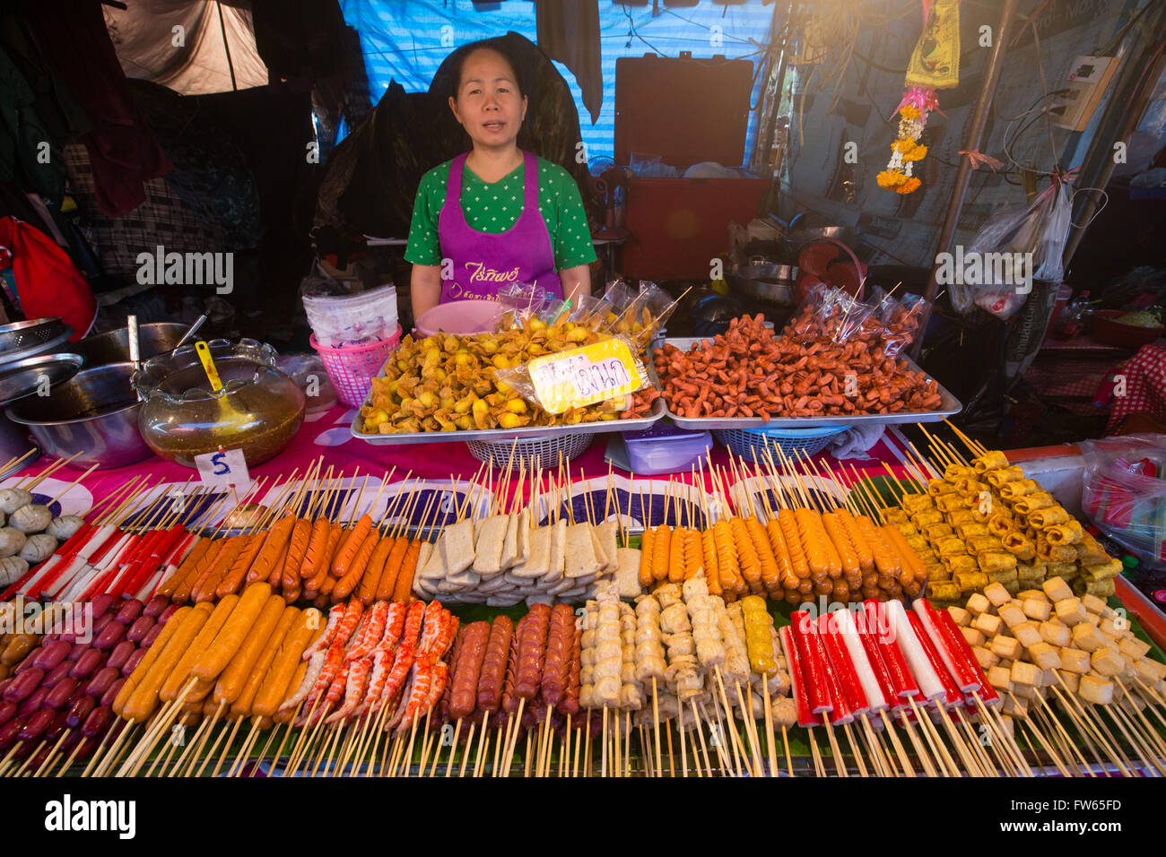 Woman at market stall with various skewers with meat, fish and sausage, food stall, food for sale at a night market, - Stock Image