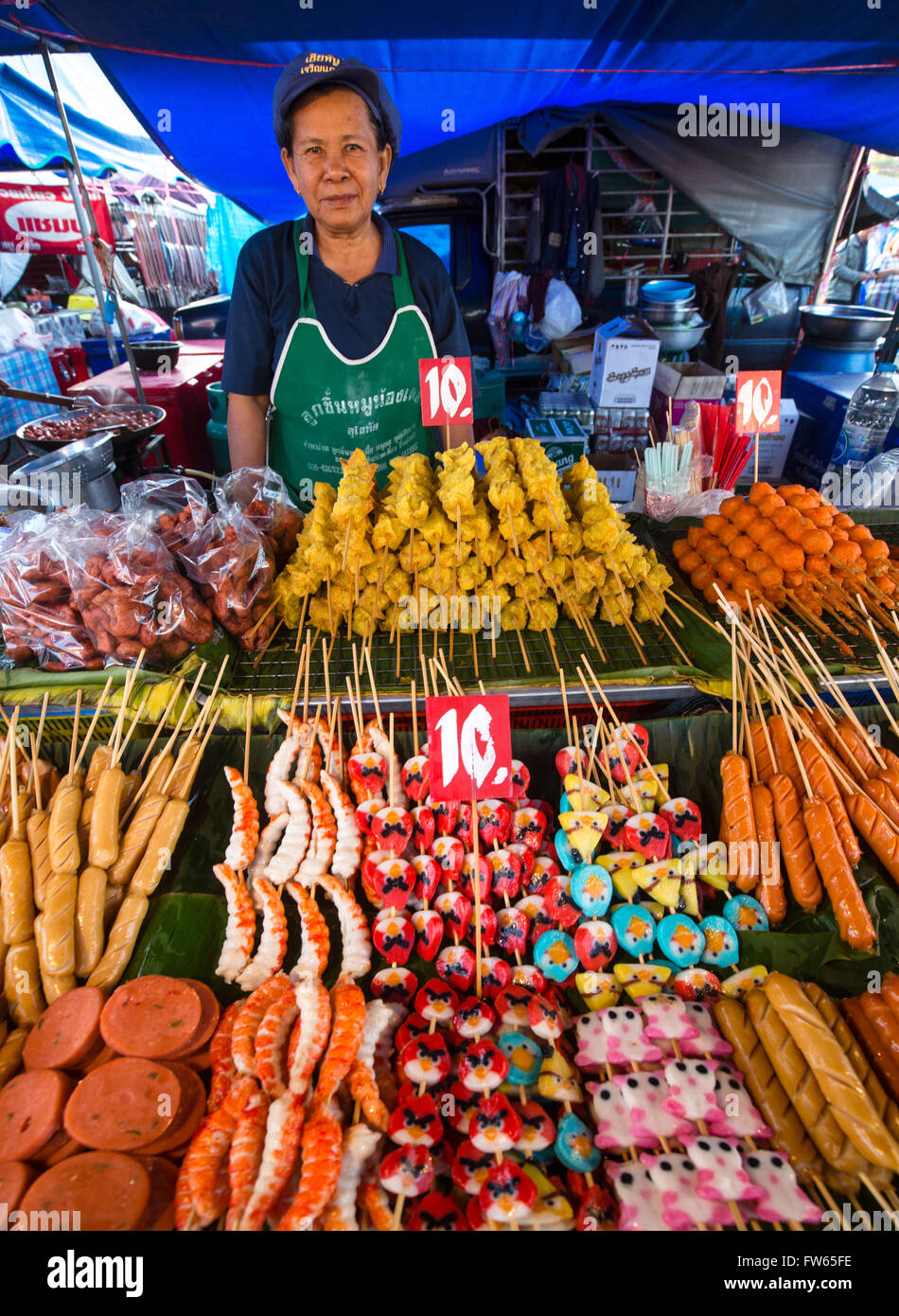 Market stall with various skewers with meat, fish and sausage, food stall, food for sale at a night market, Thailand - Stock Image