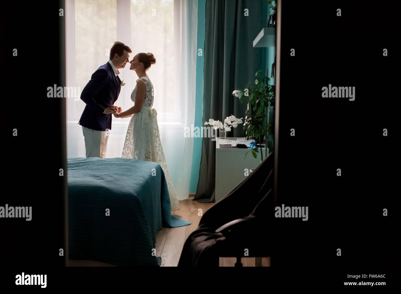 Photo full of dark silhouette of bridal couple bride and groom kissing in window  Interior bedrooms on indoor background, - Stock Image