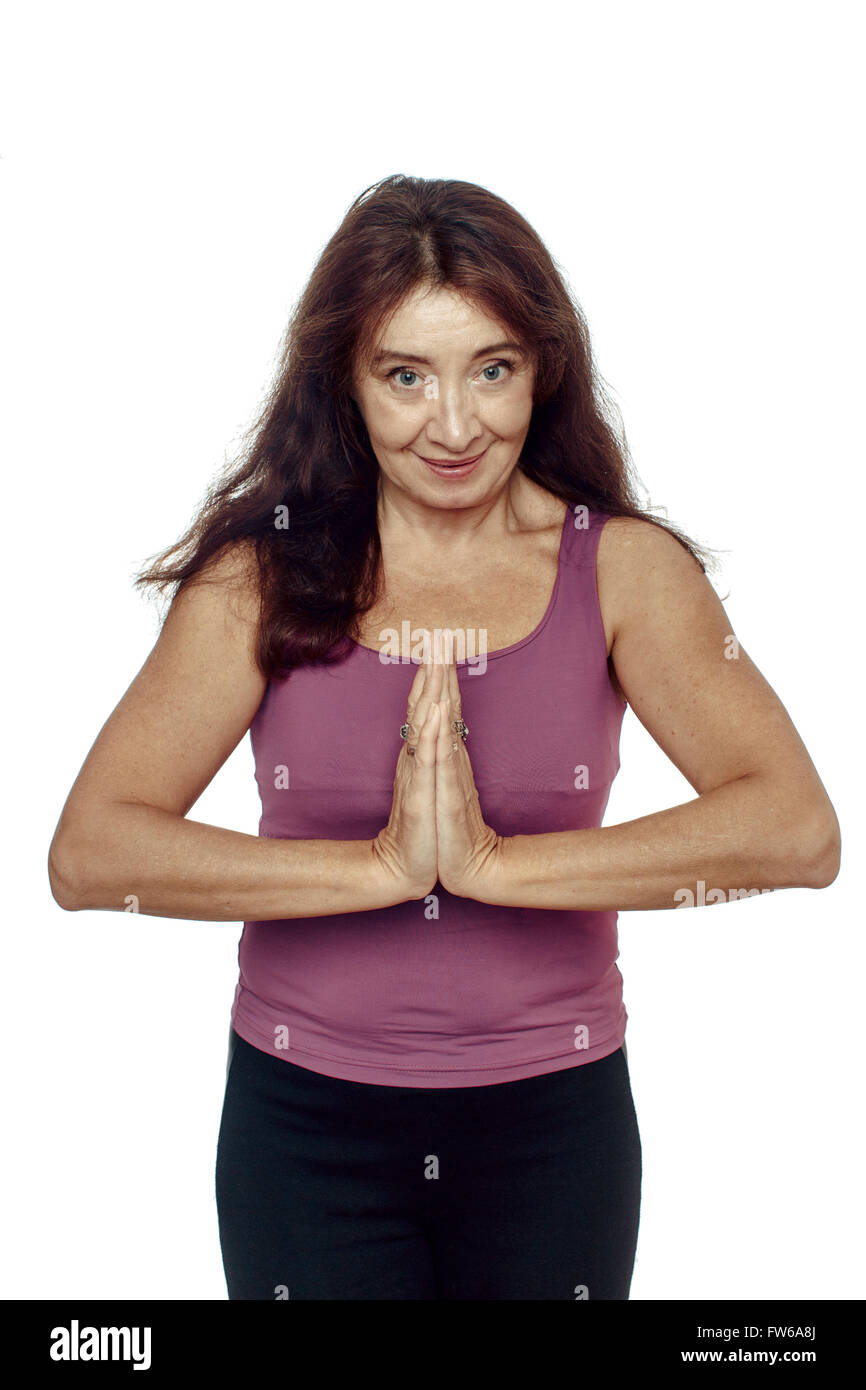 Middle-aged Woman thanks, namaste, involved in sports on a white background - Stock Image