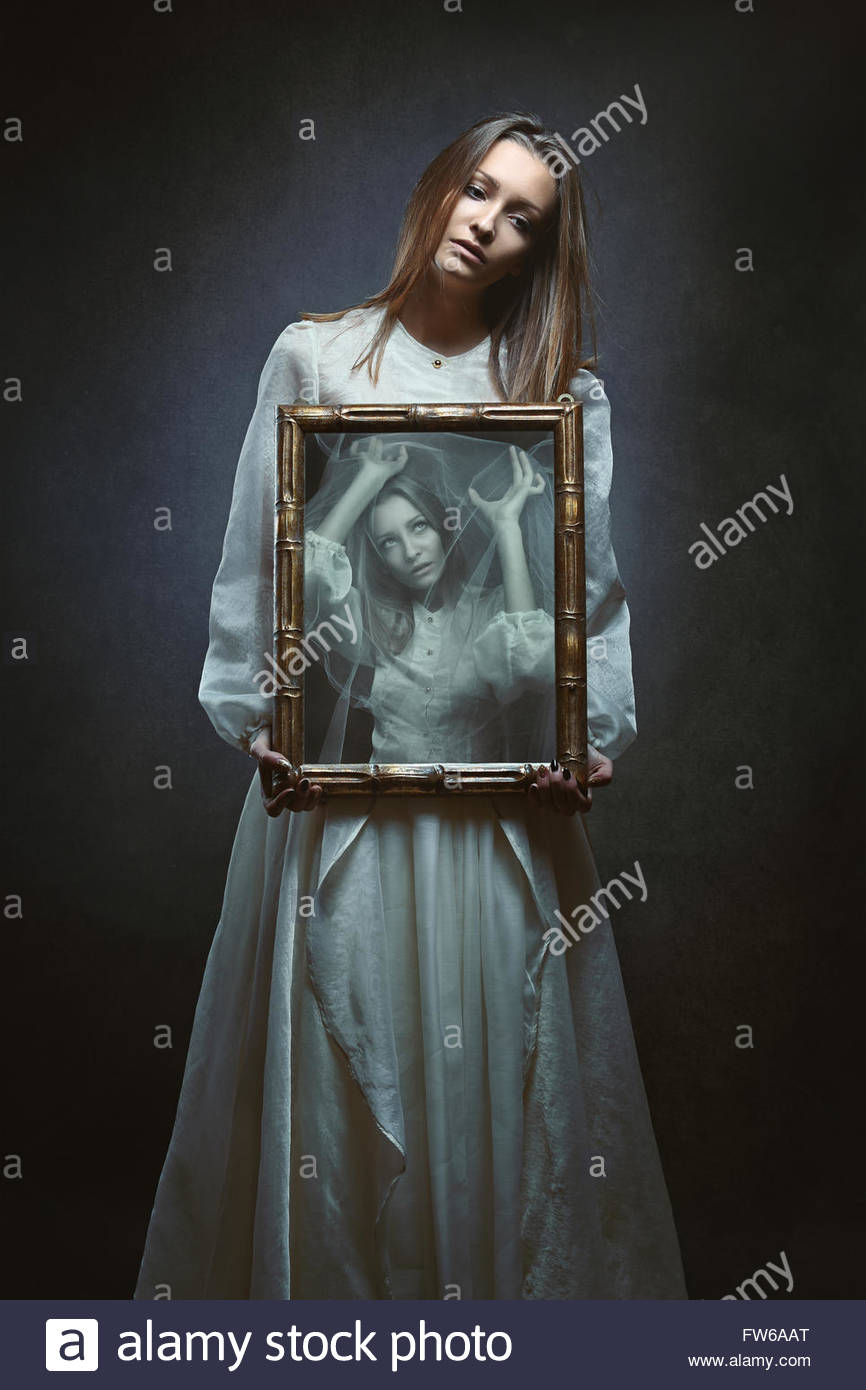 Soul of a beautiful woman imprisoned inside a mirror . Dark fantasy and surreal - Stock Image