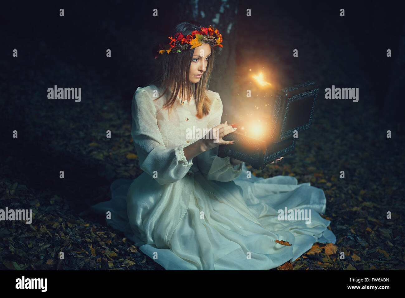 Beautiful woman opens a magical box full of fairies . Fantasy concept - Stock Image